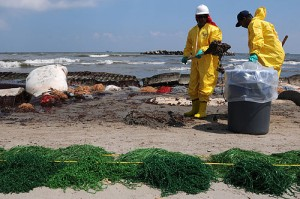 Workers contracted by BP clean up oil on a beach in Port Fourchon, La., May 23, 2010. Photo by By PO3 Patrick Kelley via Wikimedia Commons